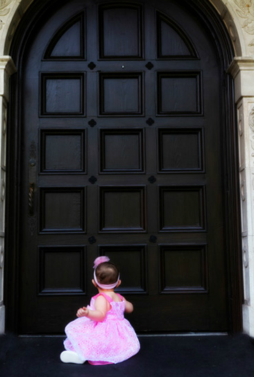 Baby staring at a large door