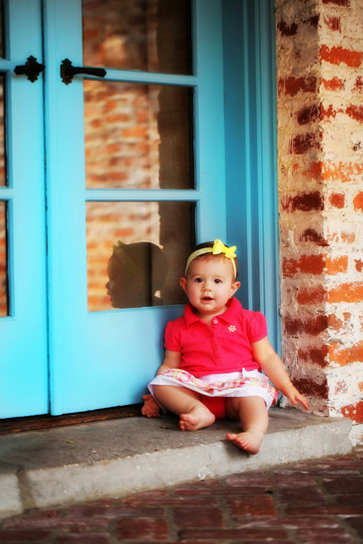 Baby sitting next to a blue door