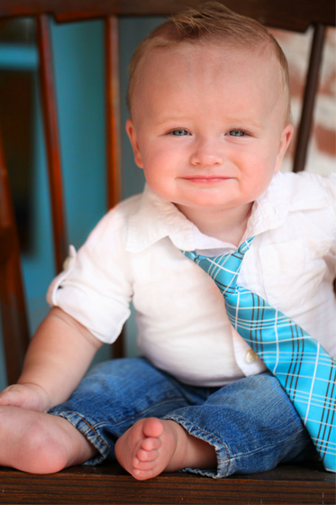 Baby wearing a striped blue tie and jeans.
